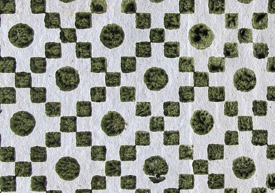 Papier dominoté. Motifs géométriques : Damier en diagonale composé de carrés alignés sur la pointe, et d'un gros point au centre des espaces ainsi formés. Impression verte sur papier blanc